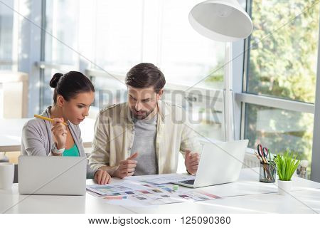 Portrait of attractive young freelancers working together. They are sitting at the table and looking at the sketches of apartment with concentration. The woman is holding a pencil