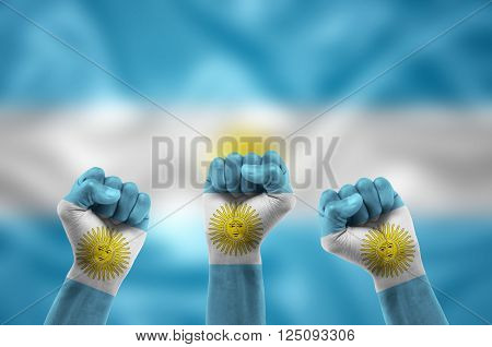 Argentine fans with hands painted with the Argentine flag celebrating victory