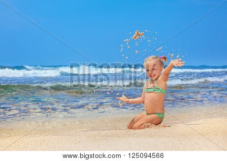 Portrait of beautiful little traveler sunbathing on sunny white sand sea beach - happy smiling baby girl has fun. Active travel family lifestyle water activity and games on summer vacation with child