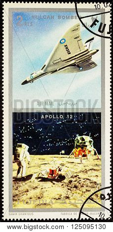 MOSCOW RUSSIA - APRIL 09 2016: A stamp printed in Fujeira shows spacecraft Apollo 12 on the Moon and Vulcan bomber series