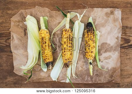 Grilled corn over oily craft paper and rustic wooden background, top view