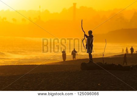 Silhouette of a boy on a beach, playing with driftwood stick