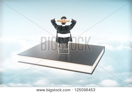 Businessman sitting on a black book soaring in the sky