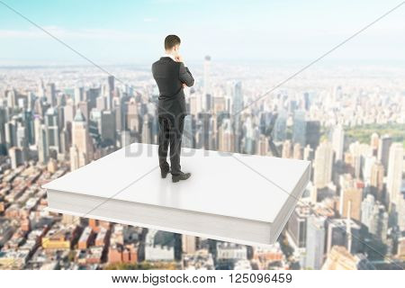 Businessman standing on a white book soaring over city