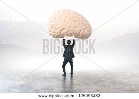 Businessman holding brain with blurry landscape in the background