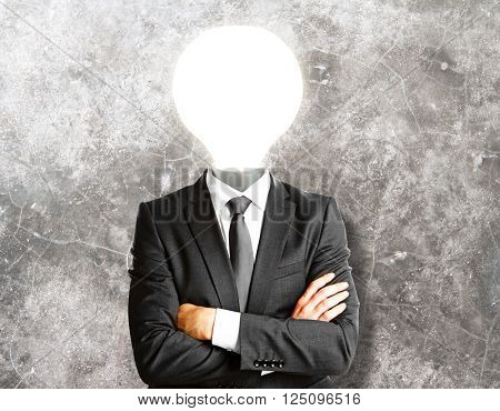 Idea concept with lamp headed businessman on concrete wall background