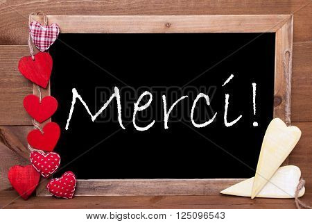 Chalkboard With FrenchText Merci Means Thank You. Many Red Textile And Wooden Yellow Hearts. Wooden Background With Vintage, Rustic Or Retro Style.