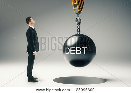 Debt concept with businessman looking at wrecking ball hanging on crane hook. 3D Rendering