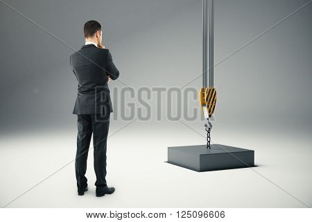 Thoughtful businessman next to black block suspended on crane hook going into hole. 3D Rendering