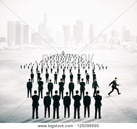 Different deirection concept with arrow shaped crowd of businesspeople going in one direction and just one person walking away on blurry cityscape background