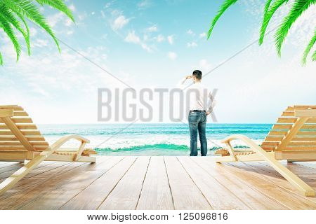 Two chaise longues and man looking into the distance at the beach