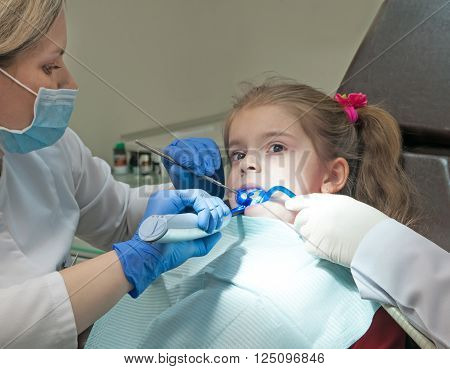 Mid section view of a dentist examining a girl teeth