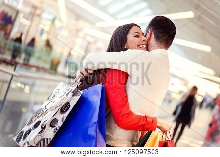 Portrait of a happy couple hugging in the shopping mall with the woman face in foreground.Sale technology and people concept - happy young couple with shopping bags.