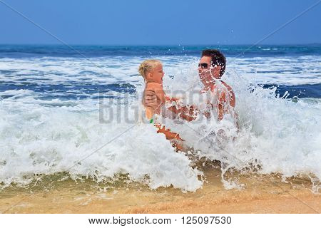 Grandfather with granddaughter play game with fun in sea surf on sea beach. Active travel family lifestyle water activity on summer vacation with child babies and grandparents