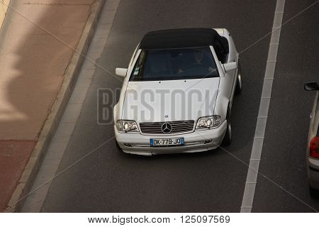 Monte-Carlo, Monaco - April 6, 2016: White Mercedes 300 SL in the Streets of Monaco. Man Driving a Mercedes 300 SL (1990) in the South of France