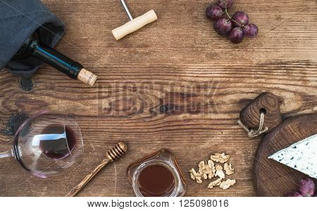 Wine and appetizer set with copy space in center. Glass of red wine, bottle, corkscrewer, blue cheese on serving board, grapes, honey and walnuts over rustic wooden table, top view