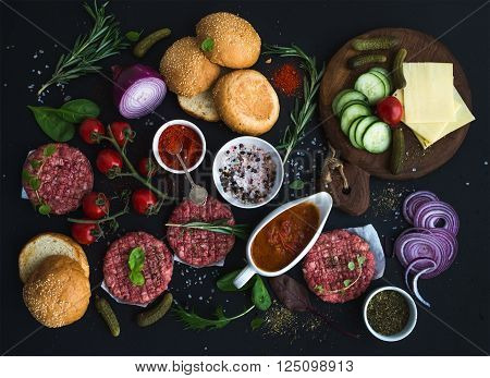 Ingredients for cooking burgers. Raw ground beef meat cutlets, buns, red onion, cherry tomatoes, greens, pickles, tomato sauce, cheese, herbs and spices over black background, top view, horizontal
