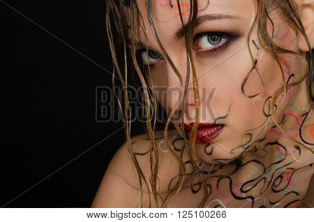 Beautiful woman with wet hair and face art on black background