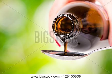 pouring a liquid on a spoon. Natural green background. Pharmacy and healthy background. Medicine. Cough and cold drug.