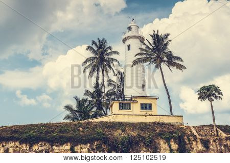Lighthouse and palm trees in the town of Galle, Sri Lanka. Galle - the largest city and port in the south of Sri Lanka the capital of the southern province and a popular tourist destination
