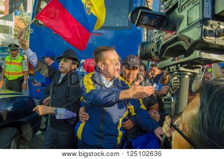 Quito, Ecuador - April 7, 2016: Closeup opposition leader Andres Paez surrounded by people, police and journalists during anti government protests in Shyris Avenue.