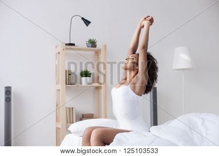 What a wonderful morning. Attractive young african woman is stretching arms after sleeping. She is sitting on bed and smiling