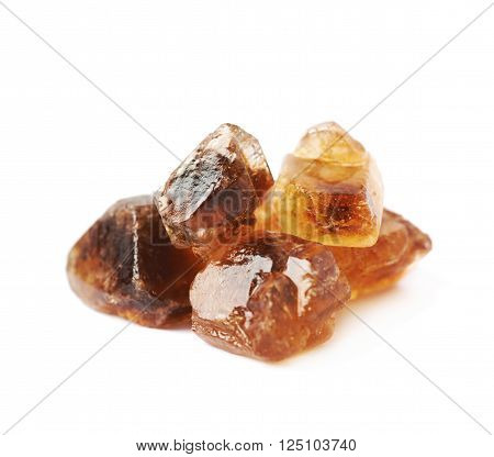 Pile of brown rock sugar crystals isolated over the white background