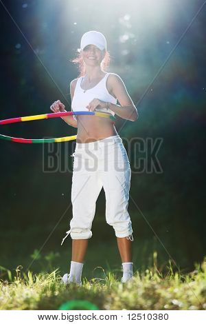 woman rotates hula hoop