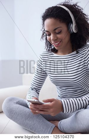 Cheerful young mulatto woman is enjoying music from headphones. She is holding a mobile phone and choosing the song. The lady is sitting on sofa and smiling