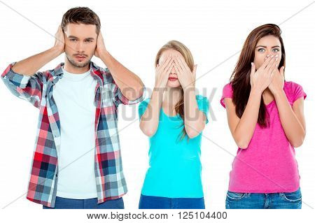 Studio shot of nice young friends. Beautiful people with eyes, ears, mouth closed looking like three monkeys. Isolated background