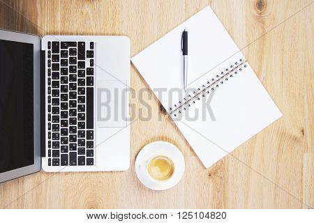 Topview of wooden table with coffee cup notebook and blank copybook with pen