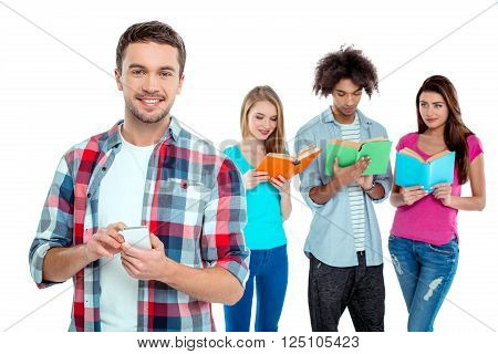 Studio shot of nice young multicultural friends. Beautiful people reading books. One boy using mobile phone, looking at camera and smiling. Isolated background
