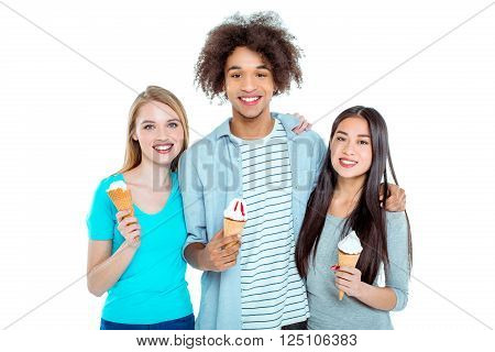 Studio shot of nice young multicultural friends. Beautiful people looking at camera, smiling and holding ice-creams. Isolated background