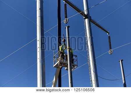 Utility workers in a boom crane basket installing utility poles