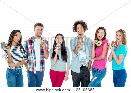 Studio shot of nice young multicultural friends. Beautiful people with cups of coffee and donuts looking at camera and smiling. Isolated background