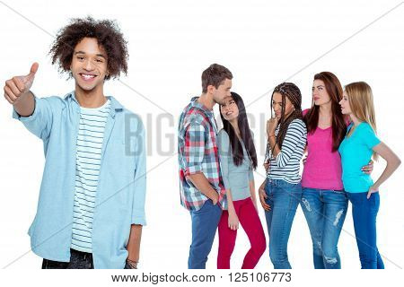 Studio shot of nice young multicultural friends. Beautiful people chatting. Focus on african boy. He looking at camera, showing thumb up and smiling. Isolated background