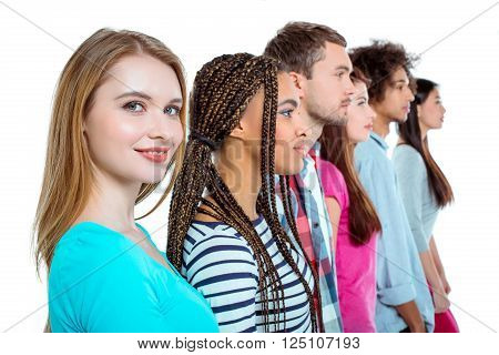 Studio shot of nice young multicultural friends. Beautiful people standing in a row. Focus on blonde woman. Girl looking at camera and smiling. Isolated background