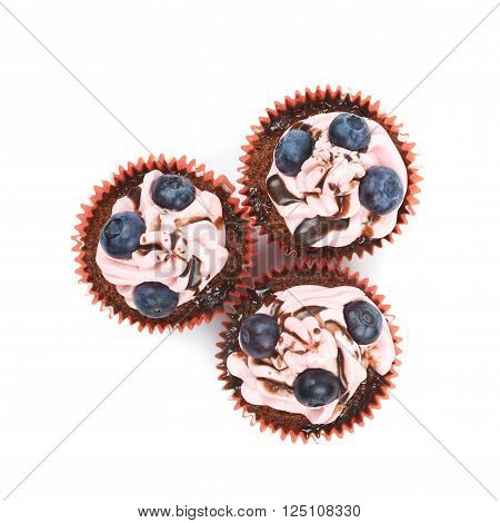 Three chocolate muffins coated with the pink cream frosting and fresh bilberries, composition isolated over the white background