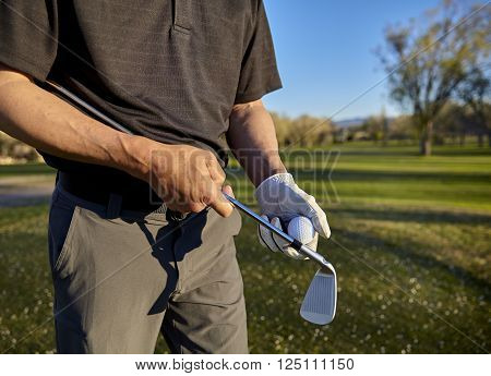 senior retired man with irons and putter on golf course