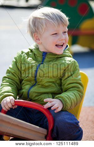 A three-year a little boy sitting on a swing at the playground in the spring outdoors