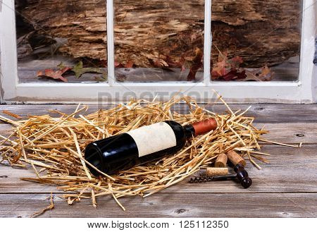 Bottle of wine on straw with old cork screw on rustic wood and window in background.