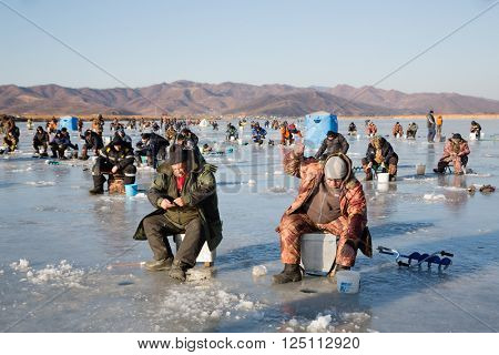 NAKHODKA, RUSSIA - DECEMBER 19, 2015: In winter, a lot of people catch fish from under the ice in the river Partizanskay. Fishing smelt and saffron cod is a popular activity among the local people.