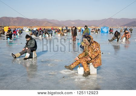 NAKHODKA, RUSSIA - DECEMBER 19, 2015: In winter, people catch fish from under the ice in the river Partizanskay. Fishing smelt and saffron cod is a popular activity among the local people.