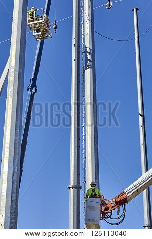 high voltage power line transmission tower workers with crane high boom lifts and blue sky