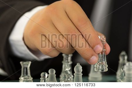 Closeup mans hands wearing suit and white shirt moving glass chess piece on game board.