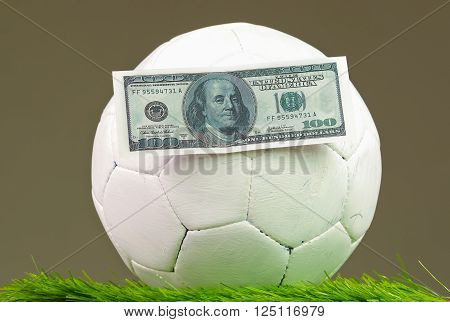 Football sitting on grass surface with dollar bills glued to it, betting concept.