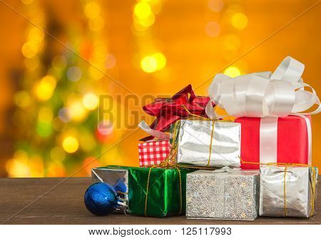 Gift boxes placed around the Christmas tree lights on trees and beautiful bokeh background.  for Christmas and happy new year.