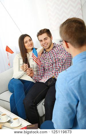 Agent offering vacation options for young couple in the office of travel company