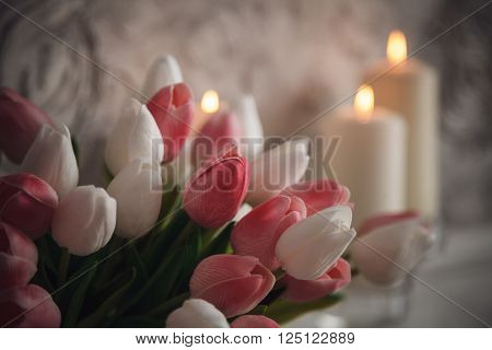 Burning Candles With Pink And White Tulips On Grey Background