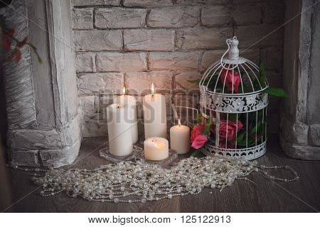 Decoration of fretwork fireplace with flowers, candles and bead